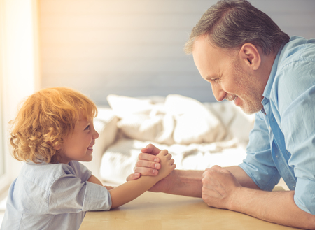 grand kid: Handsome grandpa and grandson are wrestling and smiling while spending time together at home