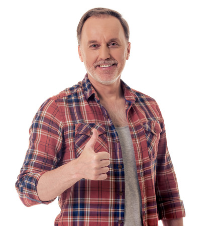 Handsome mature man in casual clothes is showing Ok sign, looking at camera and smiling, isolated on white