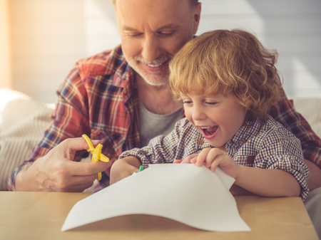 grand son: Handsome grandpa and grandson are cutting paper and smiling while spending time together at home Stock Photo
