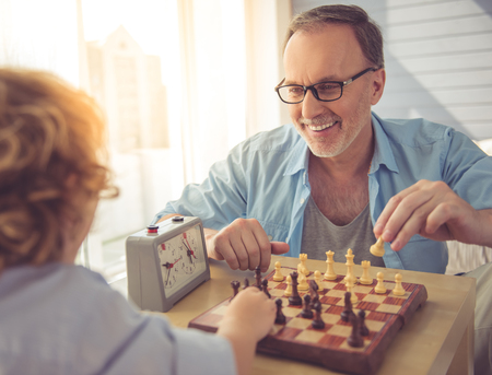 grand kid: Handsome grandpa and grandson are playing chess and smiling while spending time together at home Stock Photo