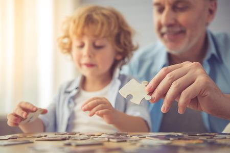 Knappe opa en kleinzoon doen puzzel en lachend terwijl hij samen tijd doorbrengen thuis
