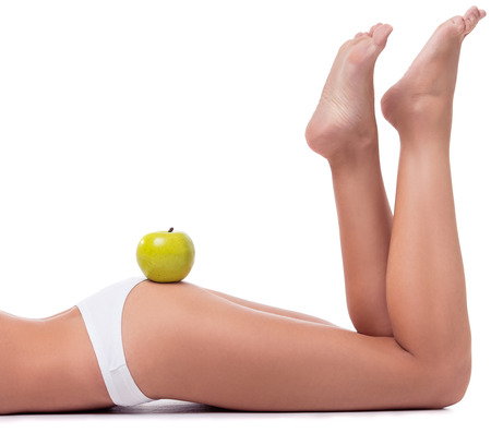 booty: Cropped image of beautiful slim girl in white lingerie posing lying with an apple on her booty, isolated on white