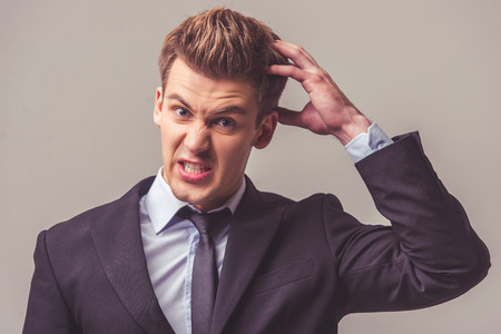 scrape: Handsome young businessman in suit is scraping his head and looking at camera, on a gray background