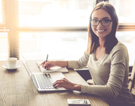 Beautiful young business lady in eyeglasses is using a laptop, making notes, looking at camera and smiling while working in office
