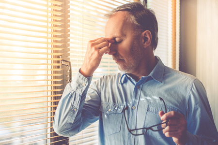 Handsome tired mature businessman is holding eyeglasses and massaging his nose bridge while standing near the window in his office