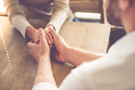 clasping: Cropped image of beautiful business lady clasping hands and man calming her