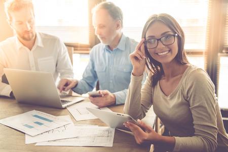 Pessoas bonitas de negócios estão usando gadgets e discutindo assuntos enquanto trabalhava no escritório. Mulher de negócios está olhando para a câmera e sorrindo Foto de archivo - 63889462