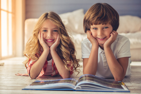 Pretty little girl and boy are reading book, looking at camera and smiling while lying on the floor at home
