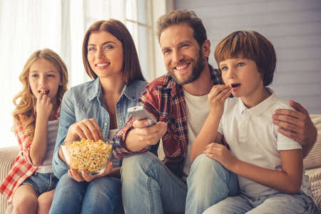 Beautiful young parents and their children are watching TV, eating popcorn and smiling while sitting on couch at home