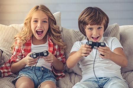 かわいい女の子と男の子は、ゲーム コンソールを再生、カメラ目線と自宅のソファに腰掛けながら笑顔