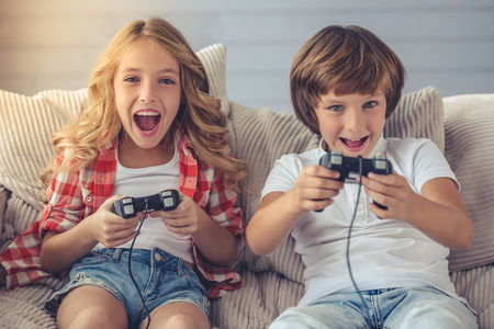 Pretty little girl and boy are playing game console, looking at camera and smiling while sitting on sofa at home