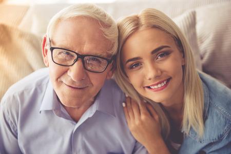 Portret van de knappe oude man en mooi jong meisje knuffelen, camera kijken en glimlachen