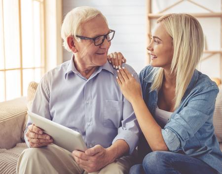 De knappe oude man en het mooie jonge meisje gebruiken een digitale tablet, spreken en glimlachen terwijl thuis het zitten op laag