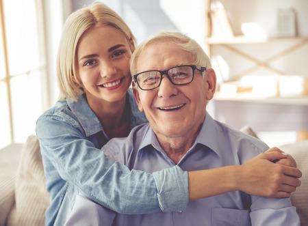 De knappe oude man en het mooie jonge meisje koesteren, bekijken camera en glimlachen terwijl thuis het zitten op laag