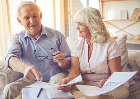 ハンサムな老人と美女は家プロジェクトについて議論して、自宅でソファに座って笑顔
