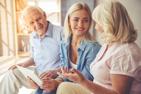 Het mooie oude paar en het jonge meisje gebruiken een digitale tablet, spreken en glimlachen terwijl thuis het zitten op laag