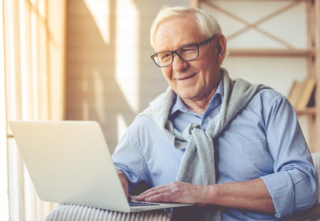 senior men: Handsome old man dressed in smart casual style and eyeglasses is using a laptop and smiling while sitting on couch at home