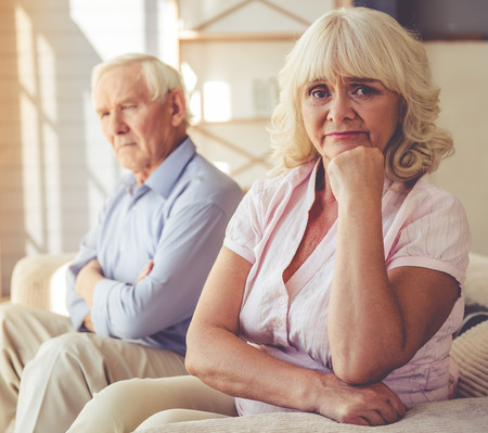 Beautiful pensive old couple is sitting apart on couch at home