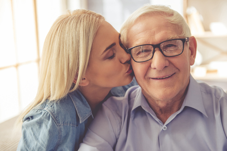 Portrait of handsome old man and beautiful young girl. Girl is kissing her parent in cheek, he is looking at camera and smiling