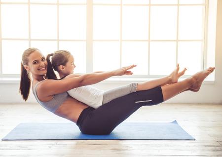 Hermosa mujer joven y encantadora niña están sonriendo mientras se hace yoga juntos en la sala de fitness Foto de archivo