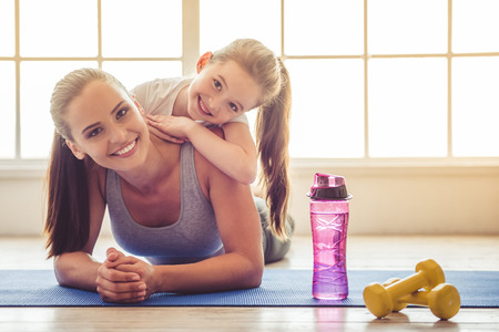 Beautiful young woman and charming little girl are looking at camera and smiling while lying on yoga mat in fitness hall Stock Photo