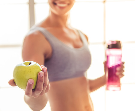 Cropped image of beautiful young sports lady smiling, holding an apple and a bottle of water