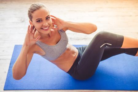 De mooie jonge sportendame bekijkt camera en glimlacht terwijl het uitwerken op yogamat in geschiktheidszaal