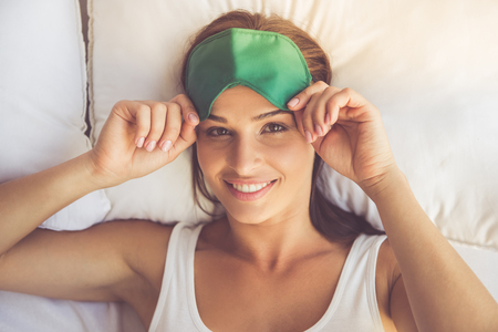 Top view of beautiful young woman looking at camera and smiling while lying in bed at home