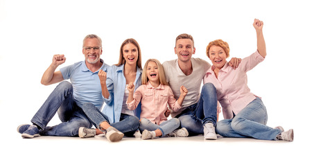 Portrait of cute little girl, her beautiful parents and grandparents looking at camera and smiling while sitting on a white background