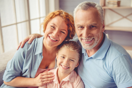 three generations of women: Portrait of beautiful happy mature couple and their little granddaughter hugging, looking at camera and smiling while sitting on sofa at home Stock Photo
