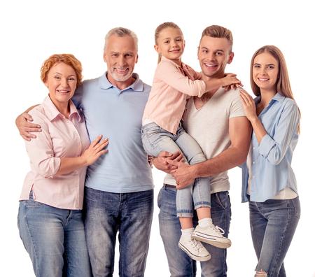 귀여운 소녀, 그녀의 아름다운 부모와 조부모는 포옹, 카메라를보고 웃 고, 화이트 절연
