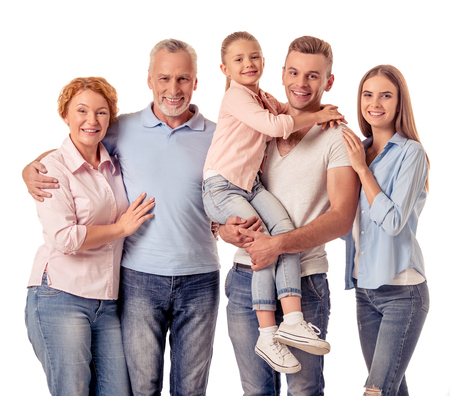 Cute little girl, her beautiful parents and grandparents are hugging, looking at camera and smiling, isolated on white
