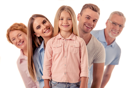 Portrait of cute little girl, her beautiful parents and grandparents looking at camera and smiling, isolated on white