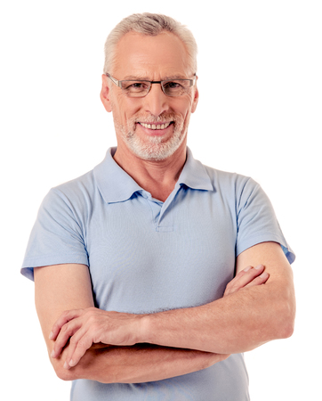 Handsome mature man in casual clothes and eyeglasses is looking at camera and smiling while standing with folded arms on a white background