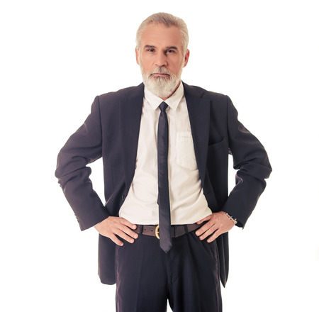 Handsome bearded mature businessman in classic suit is looking at camera while standing akimbo on a white background Foto de archivo