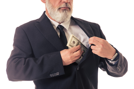 putting money in pocket: Cropped image of handsome bearded mature businessman in classic suit putting money into the inner pocket of his jacket, isolated on white