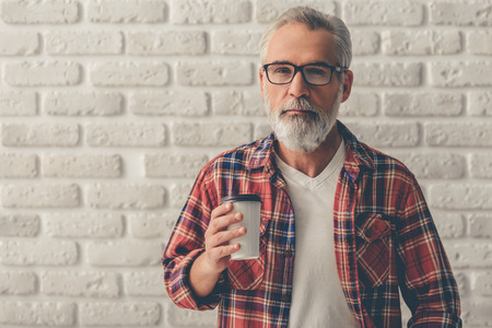 Handsome bearded mature businessman in casual clothes and eyeglasses is holding a cup of coffee and looking at camera, on a white brick wall background
