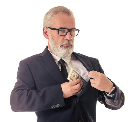 putting money in pocket: Handsome bearded mature businessman in classic suit and eyeglasses is putting money into the inner pocket of his jacket and looking at camera, isolated on white Stock Photo