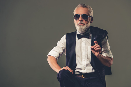 finger bow: Handsome bearded stylish mature man in shirt, waistcoat, bow tie and glasses is holding his jacket on finger and looking away, on a gray background