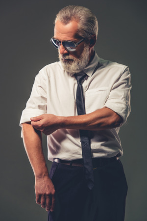 rolling up: Handsome bearded mature businessman in classic shirt and glasses is rolling up his sleeves, on a gray background Stock Photo