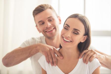 Knappe jonge man doet zijn mooie vriendin massage en lacht terwijl ze rusten thuis Stockfoto