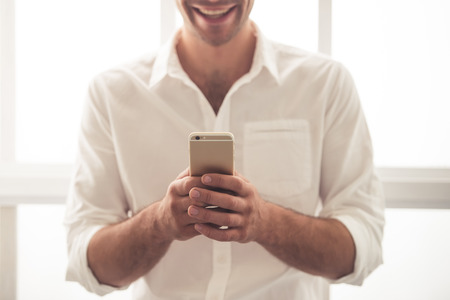 Cropped image of handsome young businessman in classic shirt using a smartphone and smiling while standing near the window