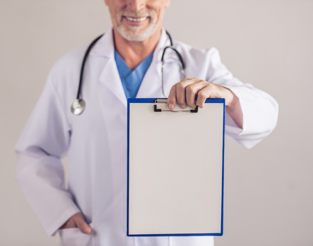 Cropped image of handsome mature medical doctor in white medical coat holding a folder and smiling, on gray background Stock Photo