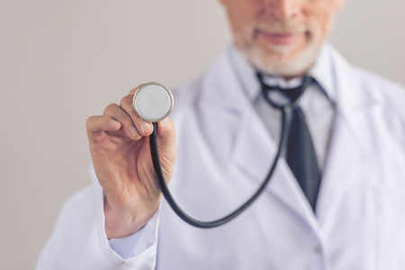 sound therapist: Cropped image of handsome mature medical doctor in white coat using a stethoscope, on gray background