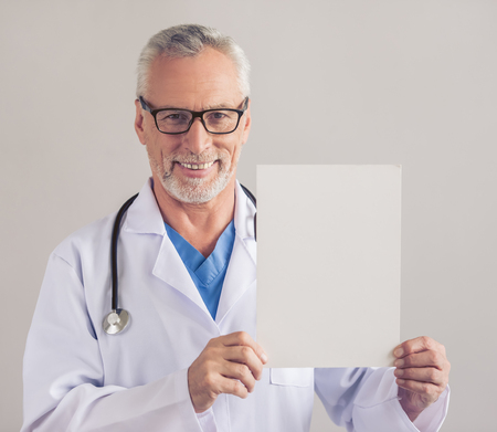 Handsome mature medical doctor in white medical coat and eyeglasses is holding a sheet of paper, looking at camera and smiling, on gray background