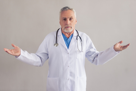 lifting hands: Handsome mature medical doctor in white medical coat is lifting hands in dismay and looking at camera, on gray background Stock Photo