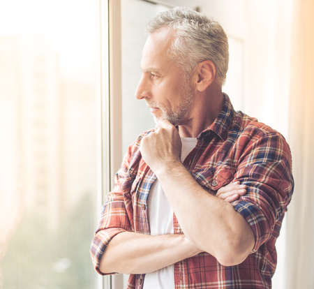 Handsome mature man in casual clothes is rubbing his chin, looking out the window and smiling while standing at home