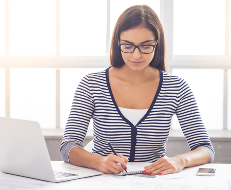 Beautiful business lady in smart casual wear and eyeglasses is making notes while working in office