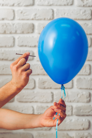 adult oops: Cropped image of handsome guy holding a balloon and a nail, on white brick wall background