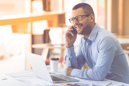 phone professional: Handsome businessman in classic shirt and eyeglasses is talking on the mobile phone and smiling while working in office